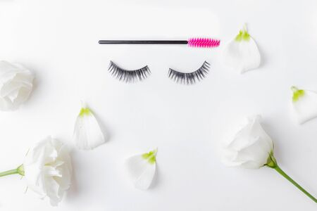 False eyelashes extensions with pink brush on white flowers background, top view. Beauty concept