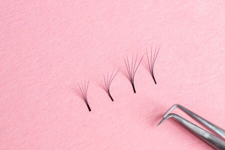 Bunches of fake lashes and tweezers on pink background. Eyelash extension procedure