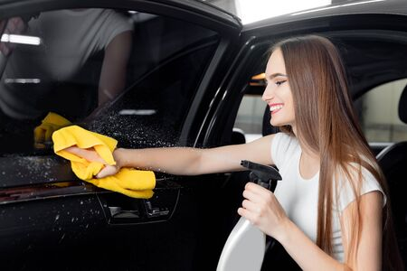Car wash service, girl worker cleaning spray eco leather interior modern microfiber and console auto