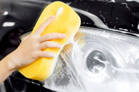 Hand woman car wash foam with yellow sponge headlights.