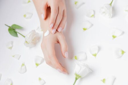 Woman applying hand cream flowers on white background, top view. Concept cosmetic body care, anti-wrinkles, anti-aging spa. Stock fotó