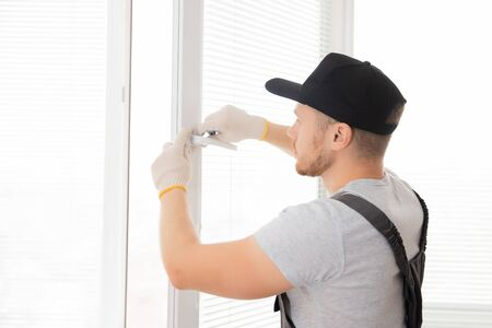 Construction worker man install plastic white upvc windows in house