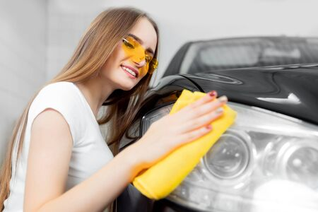 Car wash service, worker beautiful girl polishes and clean microfiber headlights on black auto
