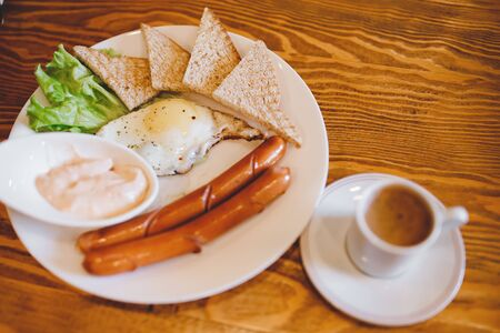 Classic English breakfast with espresso coffee in white mug, two sausages, fried eggs, toasts, lettuce on wooden background Zdjęcie Seryjne