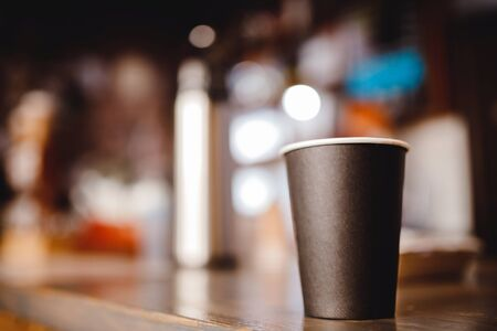 Blurred background paper cup of coffee stands on bar counter in shop, dark light bokeh