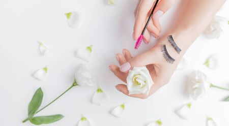 Hands girl master eyelash extension on white flowers background with pink brush, top view. Beauty concept