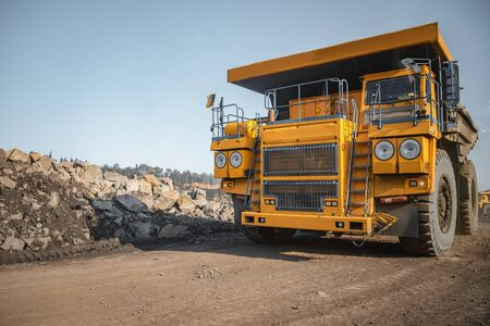Big yellow mining truck laden anthracite moves open pit coal mine Stock Photo