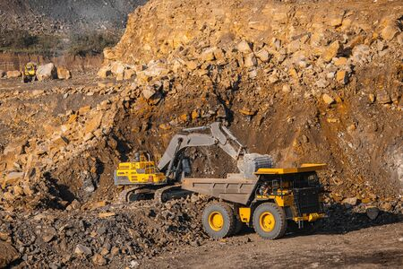 Hydraulic excavator loads gold into body of large yellow mining truck. Open pit mine industry