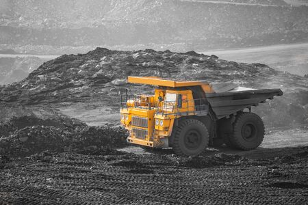 Open pit mine industry. Big yellow mining truck for coal moving on road career