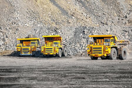 Open pit mine industry. Big yellow mining truck for coal parking garage career