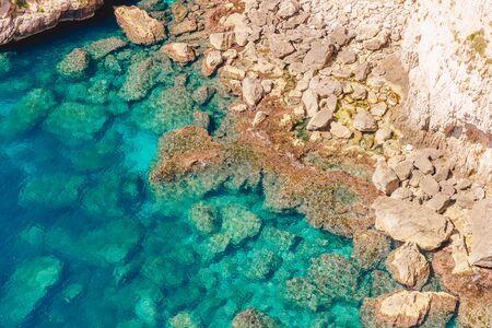 Blue Grotto in Malta. Pleasure boat with tourists runs. Natural arch window in rock Stock Photo