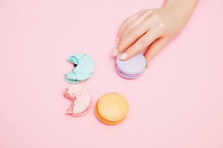 Bitten macaroons and woman hand with manicure on pink background, top view. Concept reducing interest rates on loans in banks, taxes Stockfoto