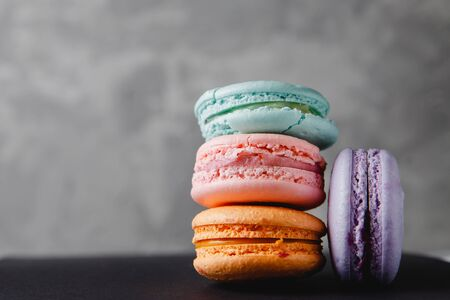 Colorful turquoise, pink, orange, purple cake French macaron or macaroon on concrete gray background