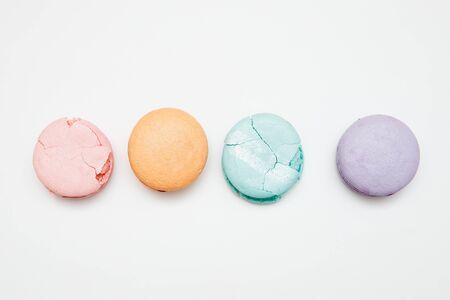 Colorful turquoise, pink, orange, purple cake French macaron or macaroon cracked on white background Stockfoto