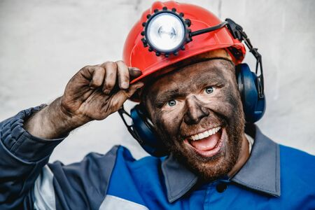 Portrait happy male miner after working in coal mine, dirty face in helmet
