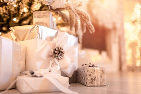 Christmas gifts box under tree with artificial snow with golden illumination. Silver color