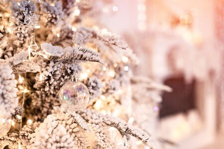 Christmas tree background with artificial snow decorated toys balls, snowflakes, branch golden illumination 版權商用圖片