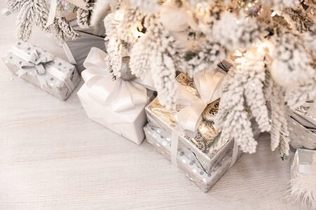 Christmas presents under New Year tree with artificial snow with golden illumination. Silver color