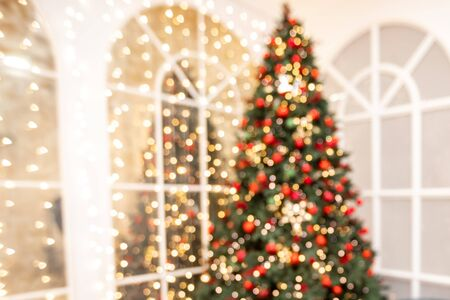 Blurred background Christmas room interior with New Year tree and gifts lights in red, green colors. 写真素材