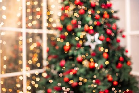 Blurred background Christmas interior with New Year tree and gifts in red, green colors.