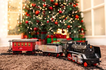 Christmas toy train with wagons in background illumination and New Year tree.