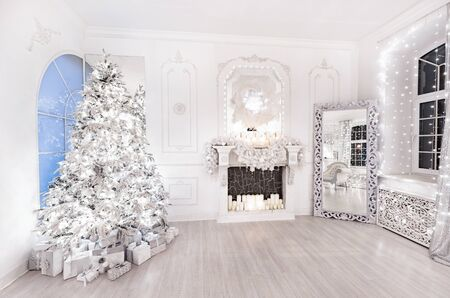 Interior Christmas room with New Year tree, fireplace and gifts in silver white light illuminations.