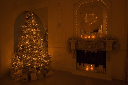 Interior Christmas background with illuminations magic glowing tree, fireplace and gifts in dark night. 版權商用圖片