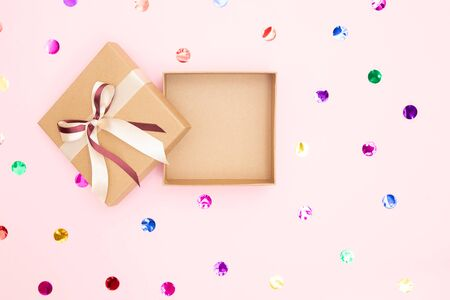 Open gift box with kraft cardboard bow on pink background with confetti, top view. Surprise concept, birthday present. Stock Photo