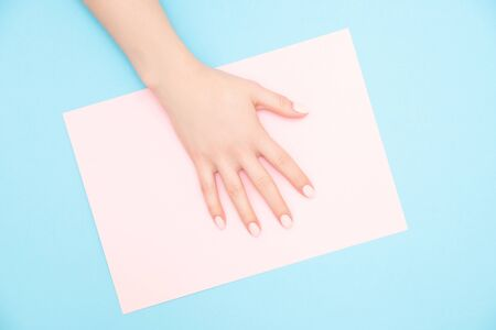 Beautiful female hands with stylish nail manicure gel polish on pink and blue background, top view. Skin care concept.