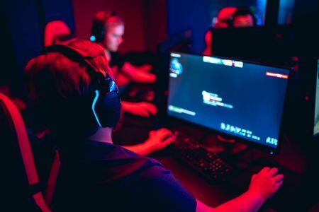 Jugador profesional de fondo borroso jugando torneos juegos en línea computadora con auriculares, rojo y azul
