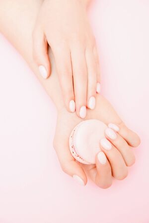 Stylish trendy female manicure on pink background. Girl holds hands macaron cookies. Concept skin care 写真素材