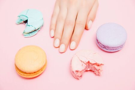Stylish trendy female manicure on pink background. Girl hands macaron cookies