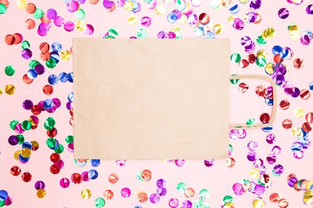 Gift box with kraft cardboard bow on pink background with confetti, top view. Surprise concept, birthday present
