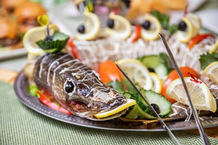 Restaurant food fish pike with lemon in mouth table snack delicious dining. Catering service