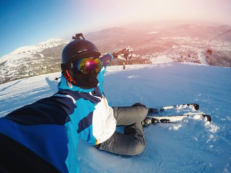 Winter extreme sport with selfie action camera. Man rides on slopes skis in protective helmet Foto de archivo