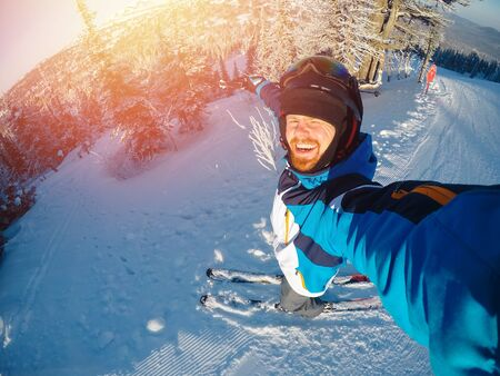 Winter extreme sport with selfie action camera. Man rides on slopes skis in protective helmet Stockfoto