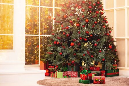 Christmas background pine tree branch with decorations red balls gifts and star, with sun light