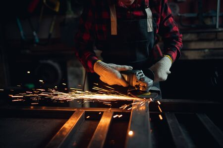 Woman working with angle grinder cuts and polishes metal after welding with spark