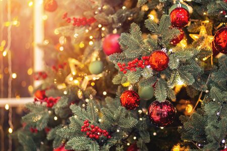 Christmas background banner pine tree branch with decorations red balls star, with bokeh light