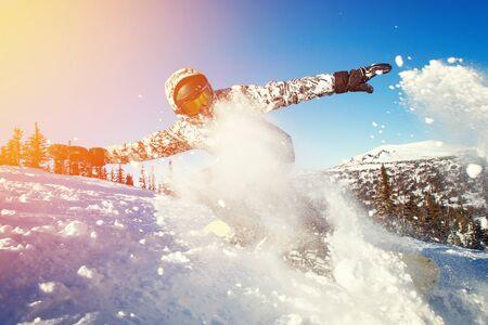 Snowboarder on snowboard rides through snow, explosion. Zdjęcie Seryjne