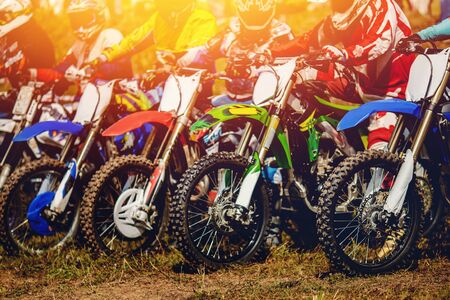 dirtbike Racers are at start of motorcycles.