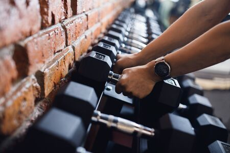 Close-up girl start watch grabs heavy dumbbell in gym with his hand. Concept lifting, fitness Archivio Fotografico