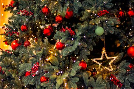 Christmas background pine tree branch with decorations red balls gifts and star, with bokeh light Stockfoto
