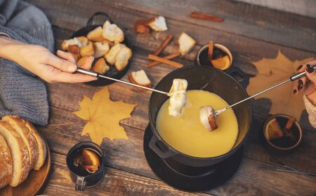 Top view friends cooking Swiss fondue assorted cheeses dinner on fire, hands holding mulled wine background wood board.