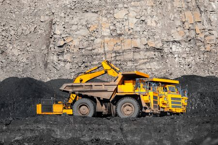 Big yellow mining truck laden anthracite moves open pit coal mine. 스톡 콘텐츠
