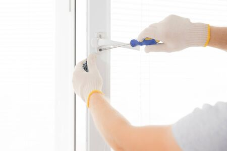 Construction worker man uses screwdriver to screw handle install plastic white upvc windows in house.