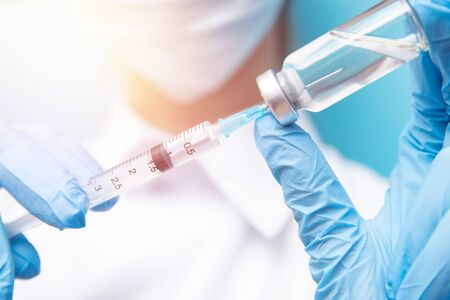 Doctor hand holding syringe and vaccine in blue gloves white coat. Disease injection concept.