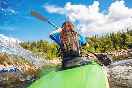 Young woman on kayak with spray paddle. Concept travel summer day.