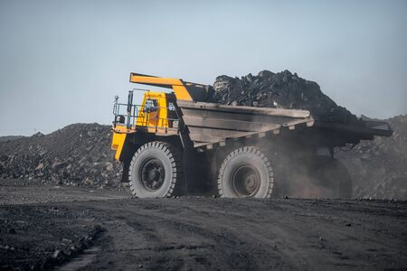 Open pit mine industry. Big yellow mining truck for coal moving on road career. 스톡 콘텐츠