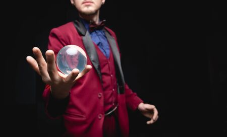Illusionist magician shows levitation trick with ball in hands on black background.